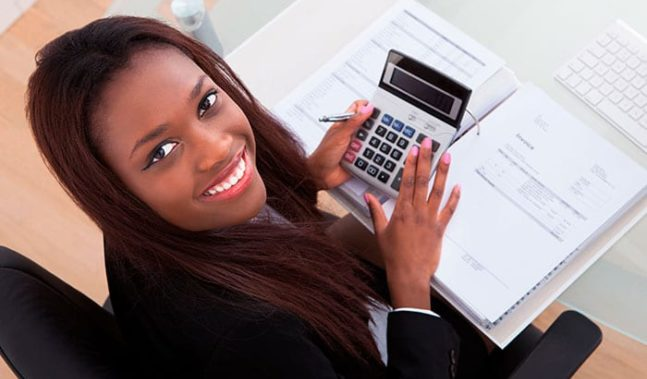 MBA finance female student smiling and working on calculator